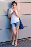 Smiling student girl using mobile phone college. Smiling student girl using mobile phone outside college modern wall Stock Photos