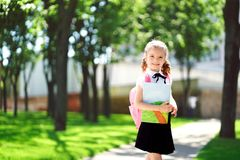 Smiling student girl wearing school backpack and holding exercise book. Portrait of happy Caucasian young girl outside stock images