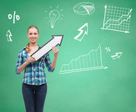 Smiling student girl with white arrow pointing up. Education, direction and people concept - smiling student girl with white arrow pointing up over green board Royalty Free Stock Photo