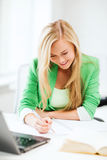 Smiling student girl writing in notebook Royalty Free Stock Image