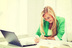 Smiling student girl writing in notebook Stock Image