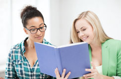 Smiling student girls reading book at school Stock Image