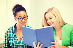 Smiling student girls reading book at school. Picture of smiling student girls reading book at school Royalty Free Stock Photography