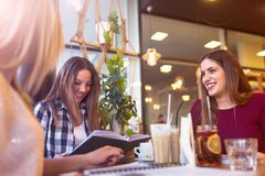 Group of female students smiling, talking in coffee shop after classes. Smiling student girls talking in coffee shop after classes. Couple of female students stock images