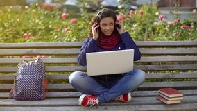 Smiling student in headphones sitting on bench, listening to favourite playlist