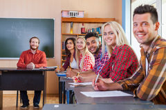 Smiling Student High School Group Write Test Looking At Camera Professor. People Sit Desk University Classroom stock photography