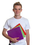 Smiling student with his paperwork. Sporty guy with blond hair and his colorful records in his hand on white background stock image