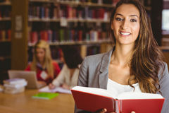 Smiling student holding a book and looking at camera Stock Photography