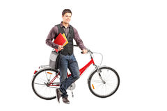 Smiling student holding books next to a bike. Full length portrait of a smiling student holding books next to a bike  on white background Royalty Free Stock Photos