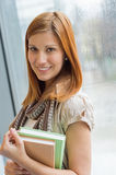 Smiling student holding books by window Royalty Free Stock Image