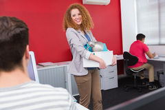 Smiling student holding box with lamp and notebook. At the college Royalty Free Stock Photography