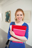 Smiling student holding folders in the hall looking at camera Stock Photo