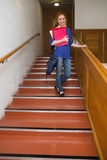 Smiling student holding folders on the stairs looking at camera Royalty Free Stock Photography