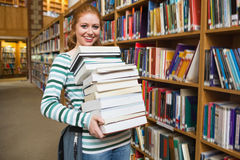 Smiling student holding heavy pile of books standing in library Stock Photography