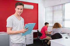 Smiling student holding notebook and phone near classmates. At the college Stock Photo