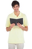 Smiling student holding a notebook. On a white background Royalty Free Stock Photo