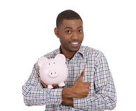 Smiling student holding piggy bank giving thumbs up Stock Image