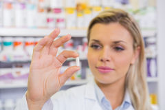 Smiling student in lab coat holding pill Stock Photography