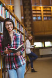 Smiling student leaning against bookshelves reading book Royalty Free Stock Image