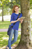 Smiling student leaning against a tree using her tablet pc Royalty Free Stock Images