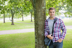 Smiling student leaning on tree looking at camera Stock Photography
