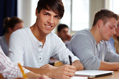 Smiling student learning in class Stock Photo