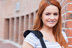 Smiling student looking at the camera. Outside a building Royalty Free Stock Photos