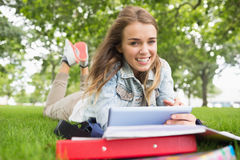 Smiling student lying on the grass studying with her tablet pc Royalty Free Stock Photography
