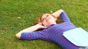 Smiling student lying on grass talking on the phone stock footage