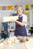 Smiling student measuring planed wood in vocational school Royalty Free Stock Photos