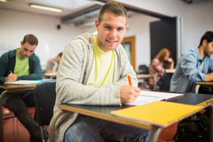 Smiling student with others writing notes in classroom. Portrait of a smiling male student with others writing notes in the classroom Stock Photography