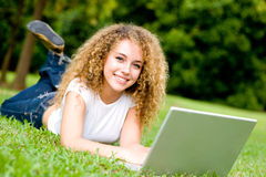 Smiling Student Outside. An attractive female student working on laptop in the park royalty free stock photography