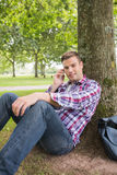 Smiling student on the phone outside leaning on tree. On college campus Royalty Free Stock Photography