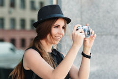 Smiling student photographs with digital camera. Royalty Free Stock Photos