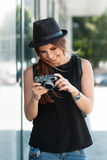 The smiling student photographs with digital mirrorless camera. Royalty Free Stock Photo