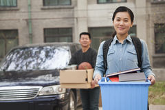 Smiling student portrait in front of dormitory at college, holding bin