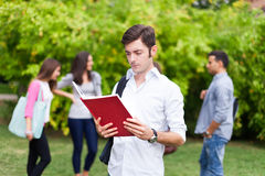 Smiling student portrait at the park. Outdoor portrait of a student reading a book Stock Image