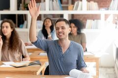 Smiling student raising hand, asking question during class in classroom