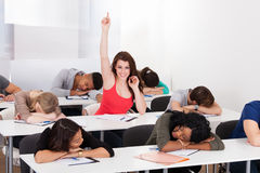 Smiling Student Raising Hand With Classmates Sleeping At Desk. Portrait of smiling college student raising hand with classmates sleeping at desk in classroom Stock Photo