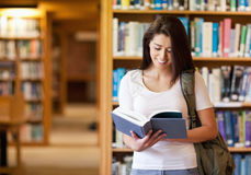 Smiling student reading a book Royalty Free Stock Photos