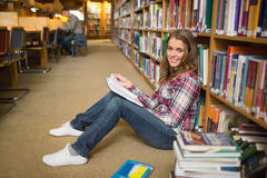 Smiling student reading book on library floor Royalty Free Stock Photo