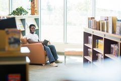 Smiling Student Reading Book In Library. Full length portrait of smiling student reading book in bookstore Royalty Free Stock Photography