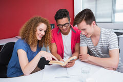 Smiling student reading book together. At the college Stock Photo
