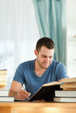 Smiling student reviewing his subject material Royalty Free Stock Image