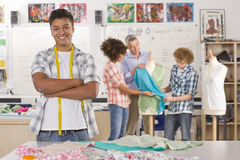 Smiling student sewing clothing in home economics classroom Royalty Free Stock Photo