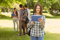 Smiling student with a shoulder bag and using tablet computer Royalty Free Stock Photography