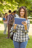 Smiling student with a shoulder bag and using tablet computer Stock Images