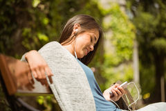 Smiling student sitting on bench text message on her mobile phone Stock Images