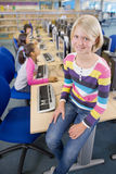 Smiling student sitting on desk in computer lab Stock Photos