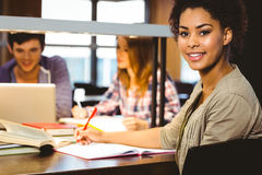 Smiling student sitting at desk writing on notepad. In library Stock Images